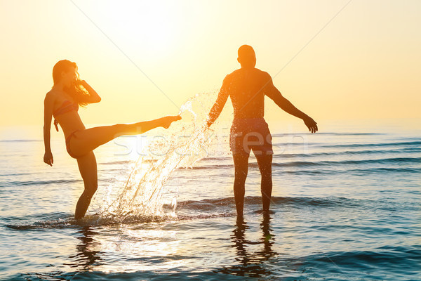 Silhouette of happy couple swimming and playing in water at suns Stock photo © DisobeyArt