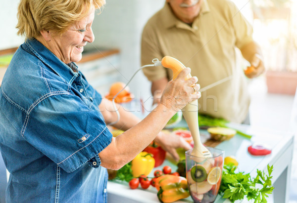 Senior couple cooking healthy vegetarian meal with fruits and ve Stock photo © DisobeyArt