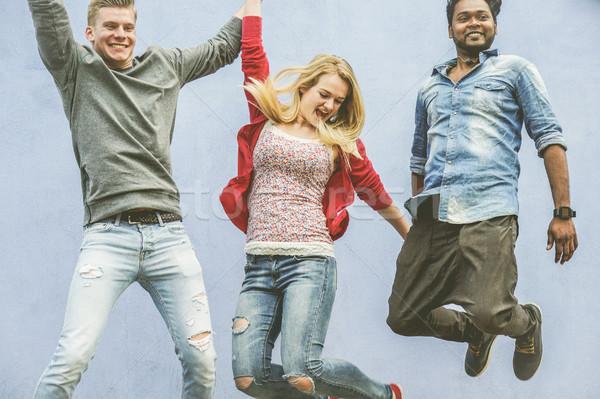 Amigos saltando ao ar livre jovem estudantes Foto stock © DisobeyArt