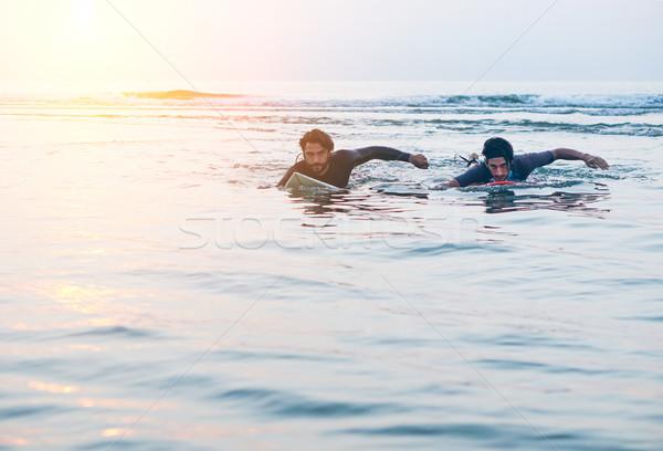 Szörfösök úszik szörfdeszka napfelkelte bent víz Stock fotó © DisobeyArt