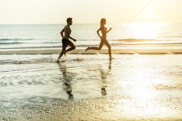 Silhouette of young happy couple running on seashore splashing w Stock photo © DisobeyArt