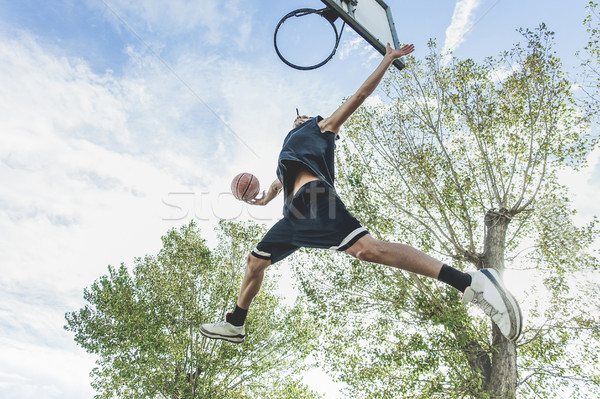 Basketball player performing huge slam dunk on the court in urba Stock photo © DisobeyArt