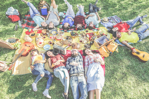 Happy friends lying down at picnic with barbecue on city park ou Stock photo © DisobeyArt