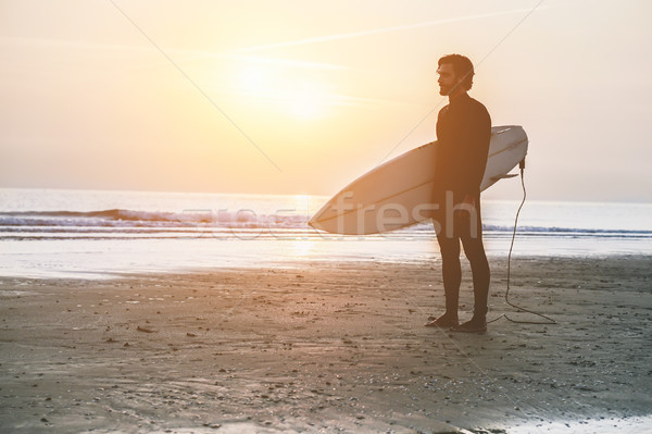 Silhouette of surfer standing on the beach waiting for waves at  Stock photo © DisobeyArt
