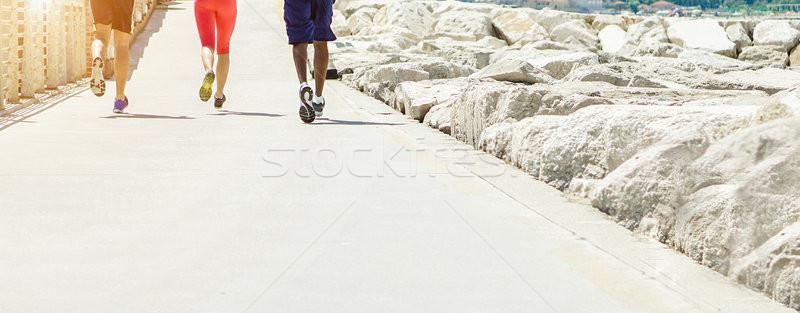 Fiatal sportolók képzés tengerpart fut út Stock fotó © DisobeyArt
