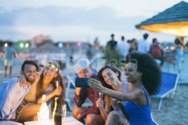 Happy friends taking selfie with smartphone at beach party outdo Stock photo © DisobeyArt