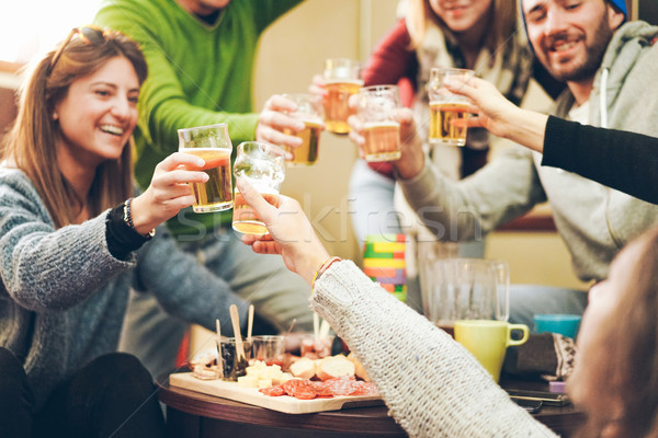 Group of happy friends cheering with beer after skiing day in ba Stock photo © DisobeyArt