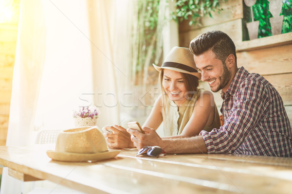 Handsome young couple having fun looking smartphone in bar cafe  Stock photo © DisobeyArt