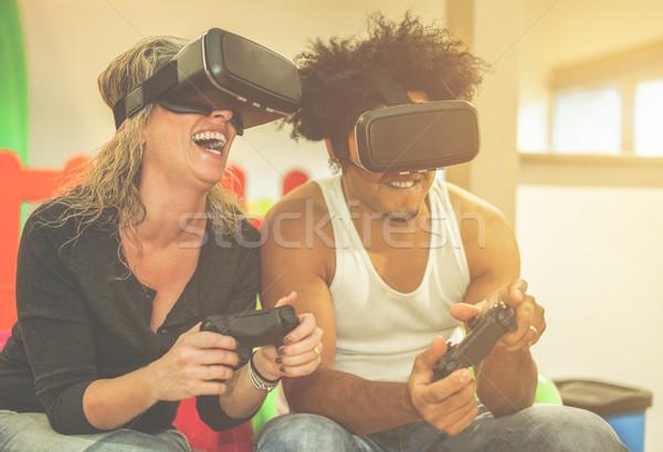 Boldog többnemzetiségű pár játszik videojátékok virtuális Stock fotó © DisobeyArt