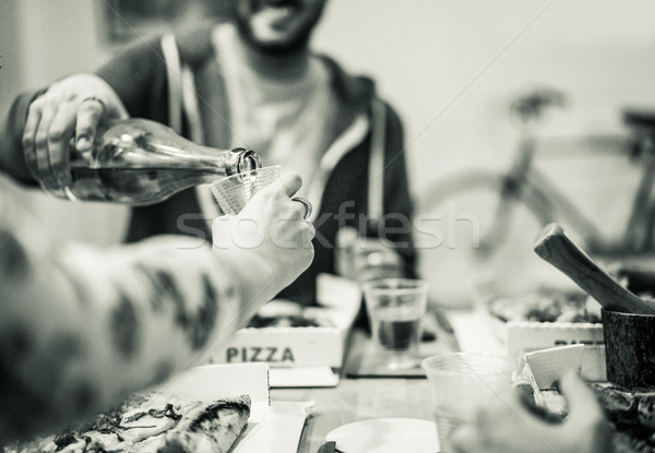 Happy friends eating pizza and drinking home brew in hostel livi Stock photo © DisobeyArt