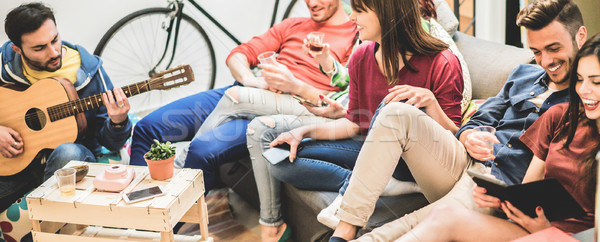 Group of happy friends having fun in hostel living room - Trendy Stock photo © DisobeyArt