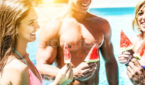 Boldog barátok eszik görögdinnye úszómedence üdülőhely Stock fotó © DisobeyArt