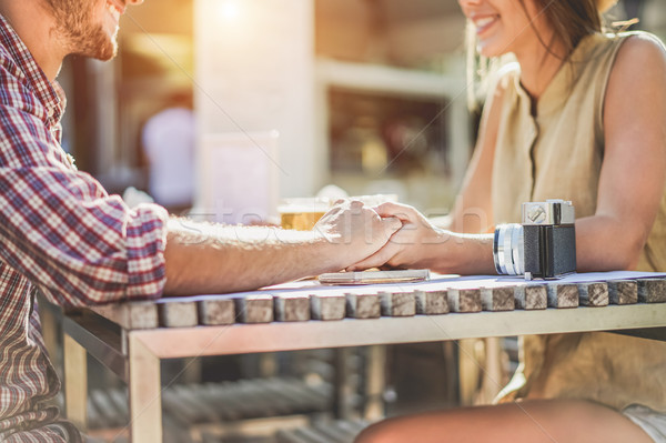 Stock photo: Young couple holding each other hands in coffee shop - Two lover