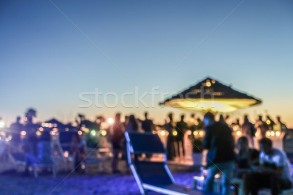 Blurred people having sunset beach party in summer vacation - De Stock photo © DisobeyArt
