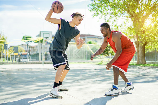 Two multiracial cheerful friends playing basketball outdoor in c Stock photo © DisobeyArt