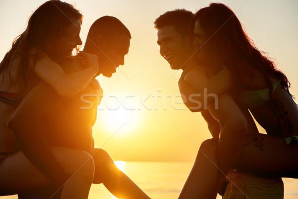 Silhouet gelukkig vrienden spelen strand zonsondergang Stockfoto © DisobeyArt