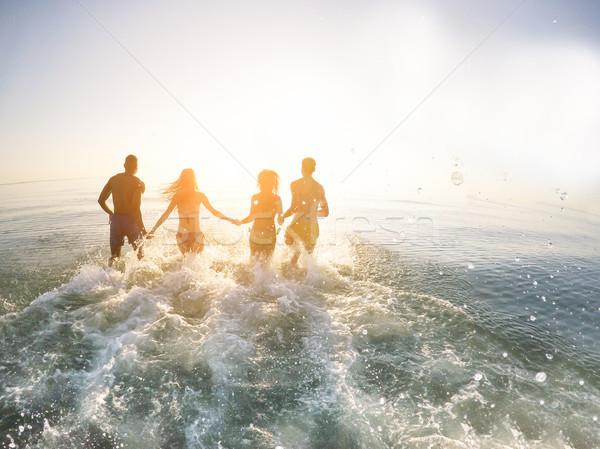 Jóvenes amigos ejecutando mar puesta de sol libertad Foto stock © DisobeyArt