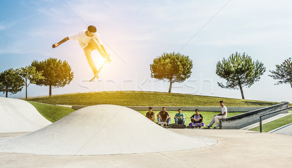 Young skater jumping with skateboard in city skate park - Sporty Stock photo © DisobeyArt
