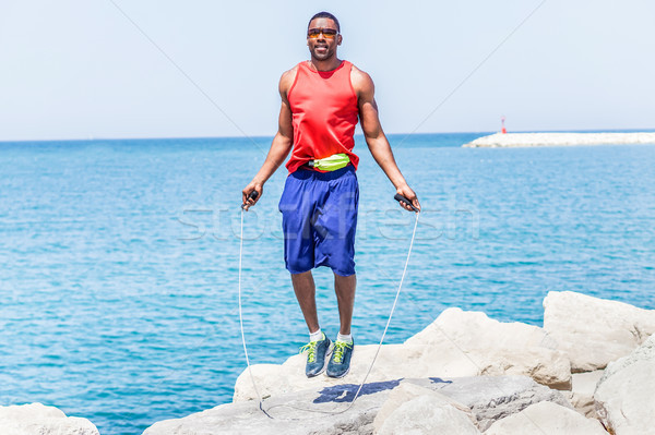 Black handsome man jumping rope with sea view in background - Ma Stock photo © DisobeyArt