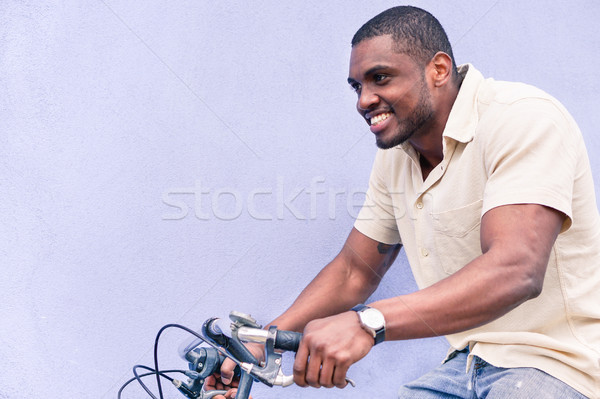 A happy African American man riding old style bicycle outdoor -  Stock photo © DisobeyArt