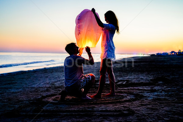 Couple of lovers lighting sky lantern on the beach at sunset - Y Stock photo © DisobeyArt