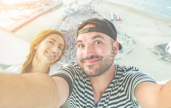 Happy young friends taking selfie on top of ferris wheel with be Stock photo © DisobeyArt