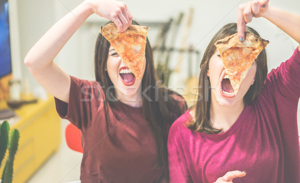 Two female friends holding pizza slices in front of their faces  Stock photo © DisobeyArt