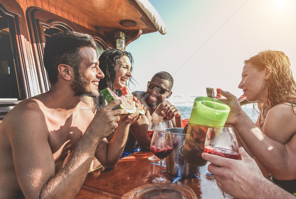 Happy friends having fun outdoors toasting sangria and eating wa Stock photo © DisobeyArt