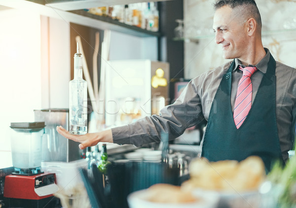 Bartender doing flair inside american bar - Barman at work perfo Stock photo © DisobeyArt