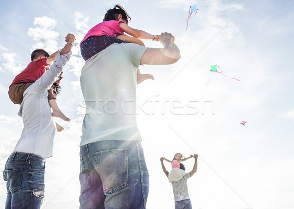 Fathers with children flying with kites and having fun on the be Stock photo © DisobeyArt