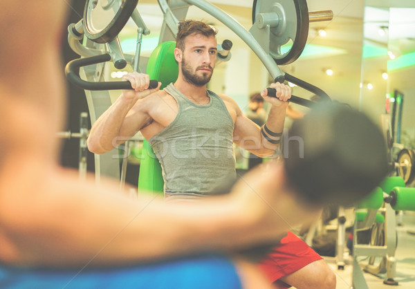 Athletes friends training with weights inside american gym club  Stock photo © DisobeyArt
