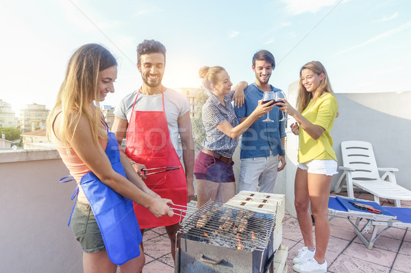 Young friends cooking meat at dinner barbecue party and drinking Stock photo © DisobeyArt