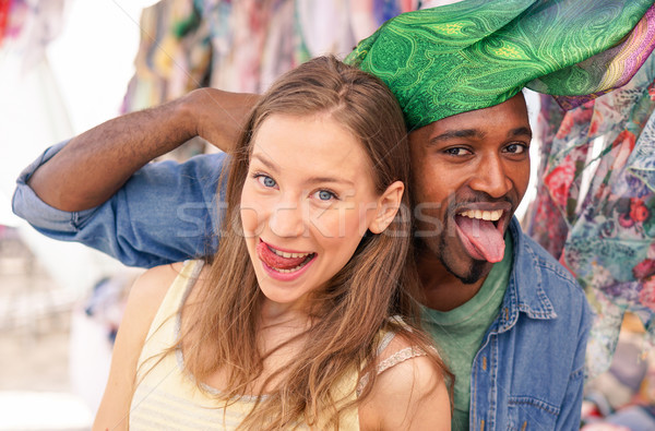 Young multiracial couple at the weekly cloth market - Best multi Stock photo © DisobeyArt