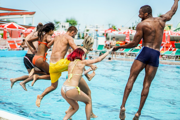 Young people looking happy while jumping into the swimming pool  Stock photo © DisobeyArt