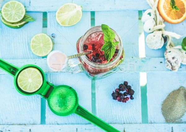 Top view of berries mojito on blue wood bar counter with lime sq Stock photo © DisobeyArt