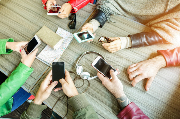 Group of friends are addicted using mobile phone devices - Upper Stock photo © DisobeyArt