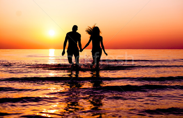 Silhouette of young fitness couple walking inside the water at s Stock photo © DisobeyArt