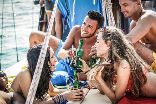 Happy friends toasting beers and chilling beers in boat vacation Stock photo © DisobeyArt