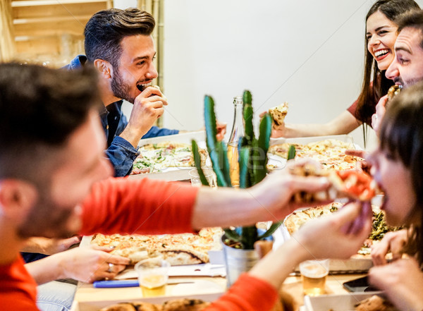 Group of happy friends eating home delivery pizza at home - Youn Stock photo © DisobeyArt