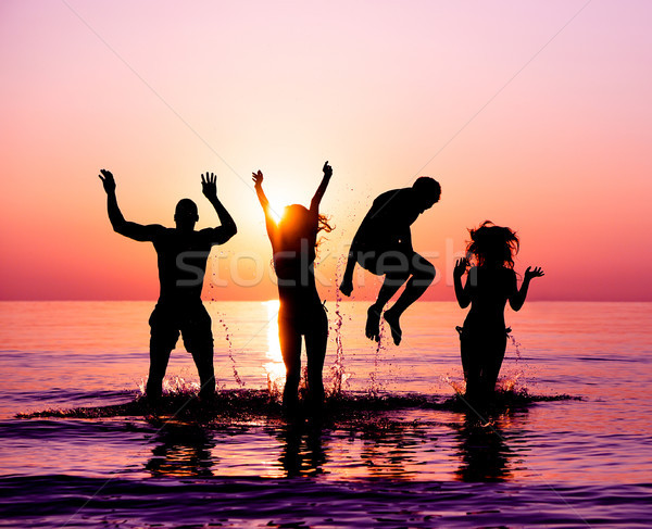 Silhouettes of happy friends jumping inside water on the beach a Stock photo © DisobeyArt