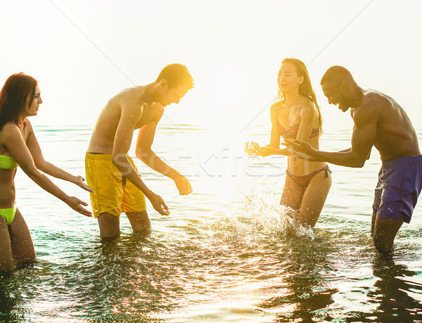 Happy friends having fun inside water for after sunrise party in Stock photo © DisobeyArt