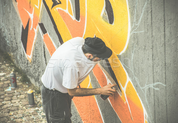 Graffiti artist covering his face while painting with aerosol co Stock photo © DisobeyArt