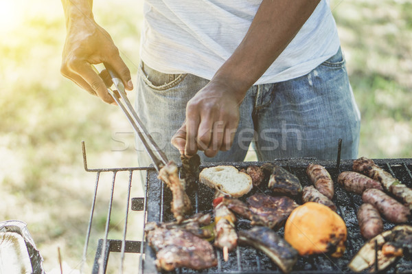 Afro american man cooking meat on barbecue - Chef putting some s Stock photo © DisobeyArt