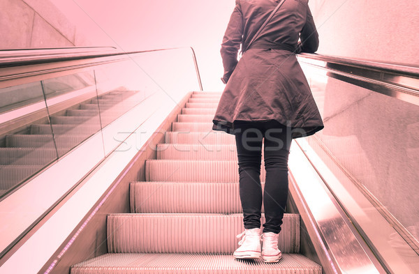 Young girl standing on escalators stairway with back light contr Stock photo © DisobeyArt