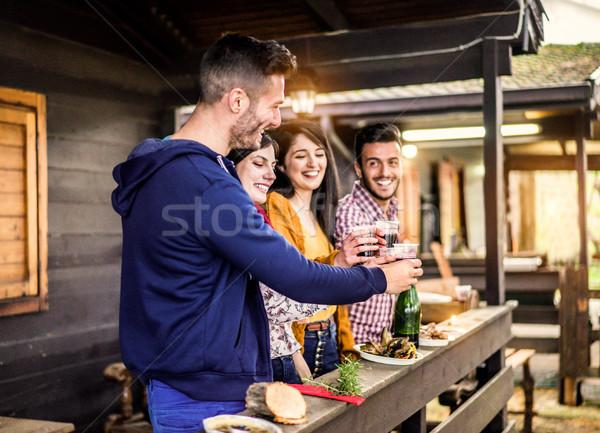 Fiatal barátok éljenez nevet fából készült bungaló Stock fotó © DisobeyArt