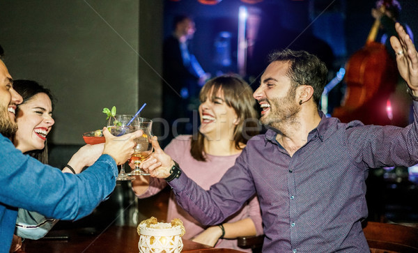 Stock photo: Group of happy friends cheering and having fun in jazz club - Yo