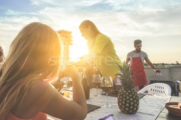Stock photo: Young friends having barbecue party at sunset on top of the roof