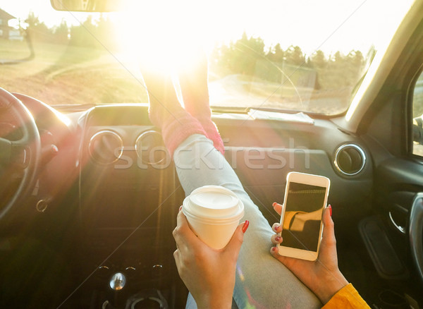 Woman toasting coffee take away go cup and using smart phone ins Stock photo © DisobeyArt