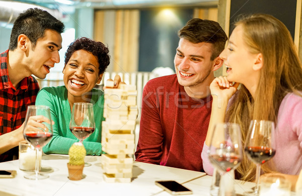 Happy friends playing board game in pub winery restaurant - Youn Stock photo © DisobeyArt