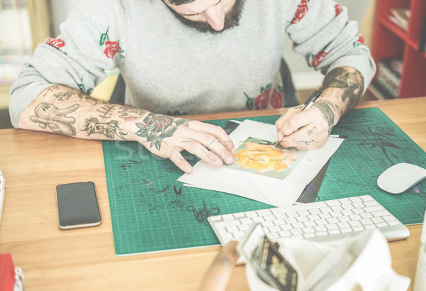 Tattoo artist drawing flower sketch inside ink studio - Hipster  Stock photo © DisobeyArt